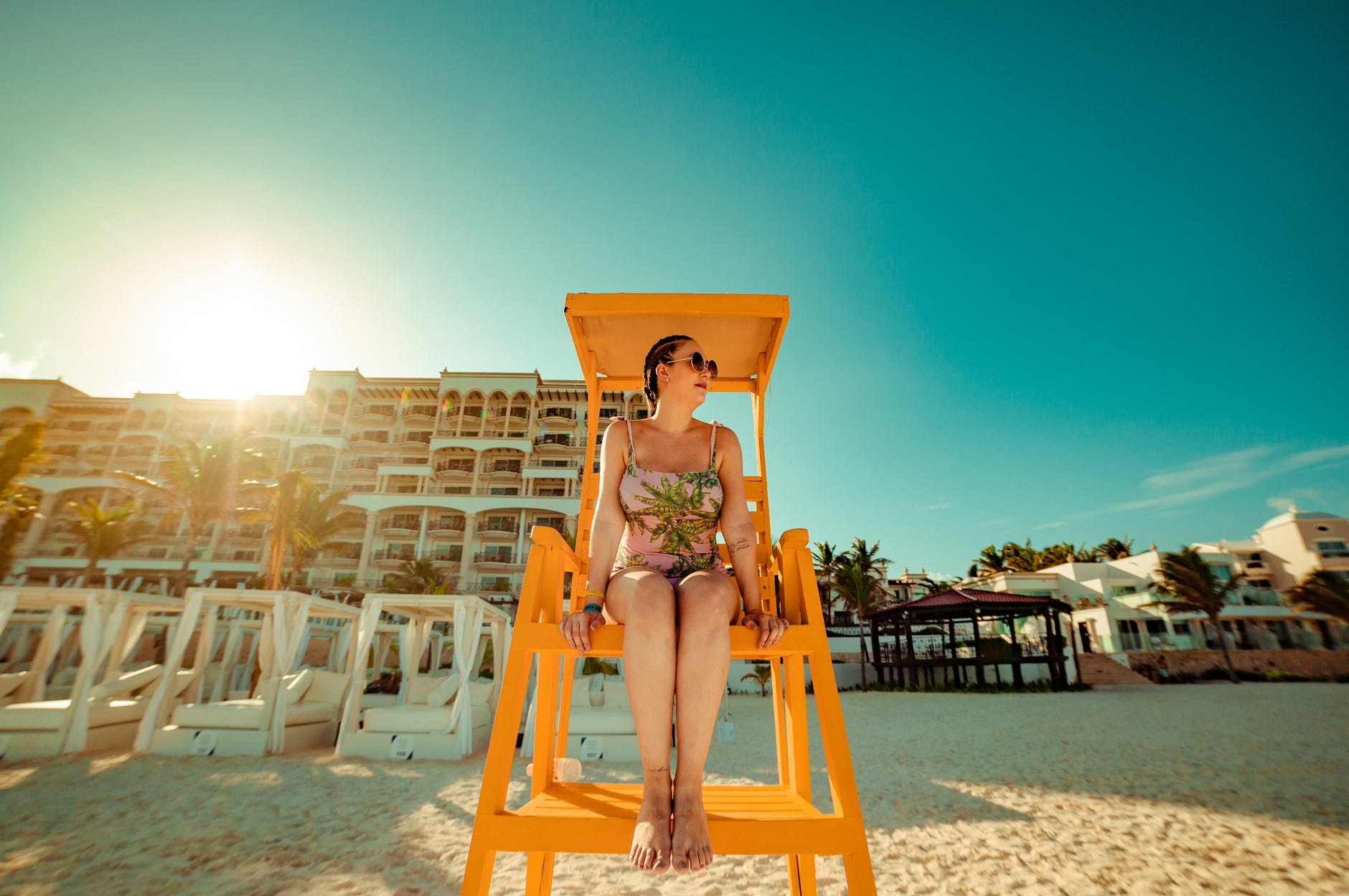 photo of woman sitting on lifeguard tower